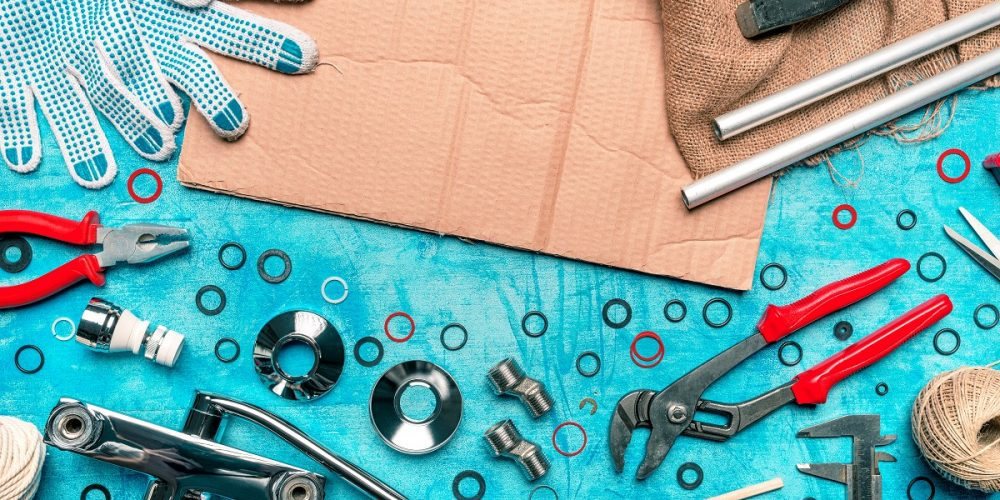 Plumbing toolkit on work desk top view flat lay, water pump wide jaw pliers and other tools